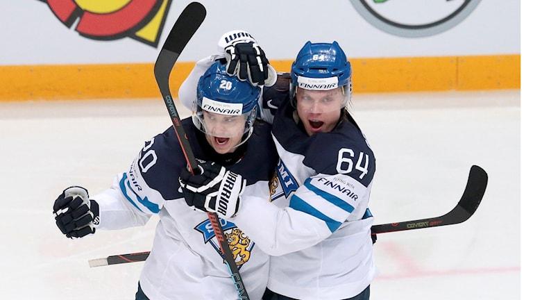 Keskellä kuvaa jääkiekkoilijat Sebastian Aho ja Mikael Grandlund juhlivat mailat koholla Ahon tekemää maalia.