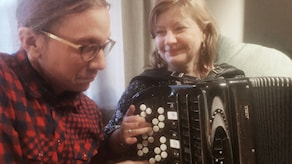 Ruutupaitainen, silmälasipäinen Eero ja vaaleatukkainen Maria soittavat yhdessä samaa haitaria. Kuva: Timo Laine/SR Sisuradio