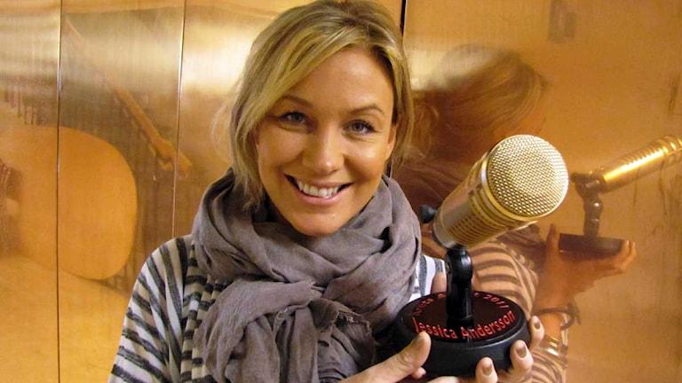 Jessica Andersson med sitt nya Svensktoppspris. En mikrofon helt i guld. Foto: Ronnie Ritterland / Sveriges Radio