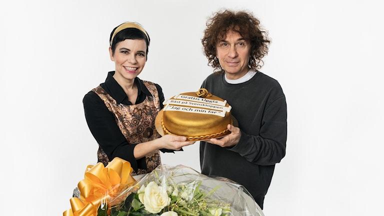 Magnus Uggla och Carolina Norén med en stor gyllene tårta.
