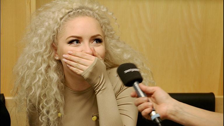 """Carolina Norén intervjuar Wiktoria som den här veckan går in på Svensktoppen med sin melodifestivallåt """"Save Me"""" håller handen för munnen och ser glad men lite chokad ut."""