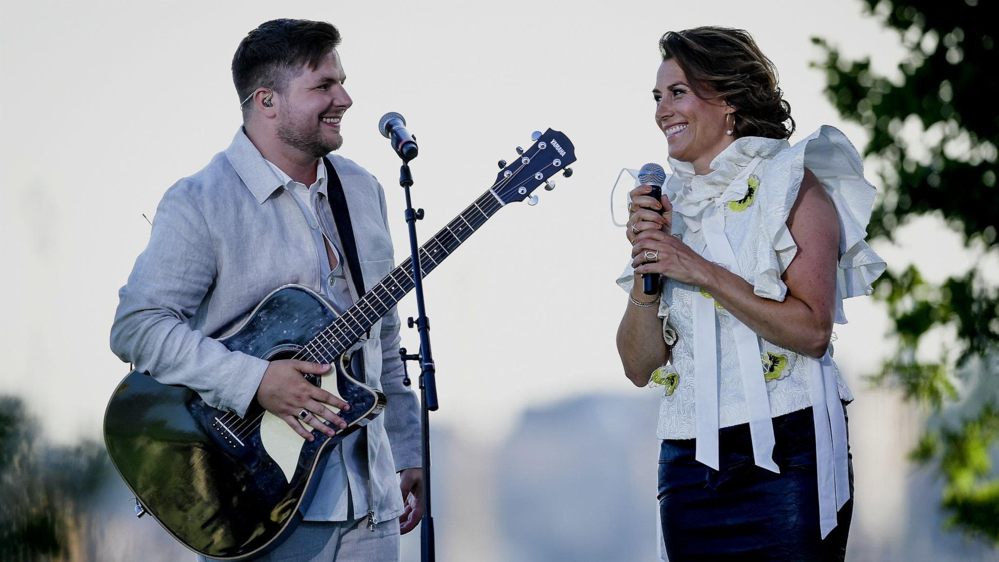 Robin står med en gitarr på scen framför en mikrofon och Jill stär jämte och håller mikrofonen med båda händerna. Båda ser jätteglada ut.