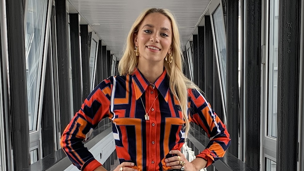 Agnes gästar P4 Musik med Carolina Norén. På bilden står Agnes i en korridor och är klädd i en färgglad tröja.