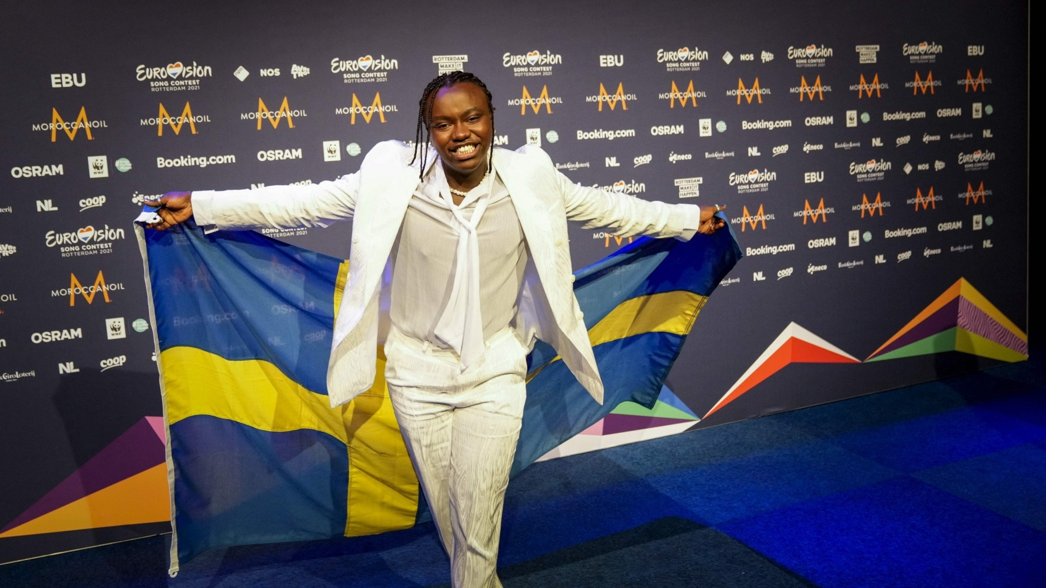 A person at a music event in front of a Swedish flag