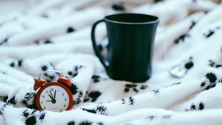 Klocka som ligger i en säng.