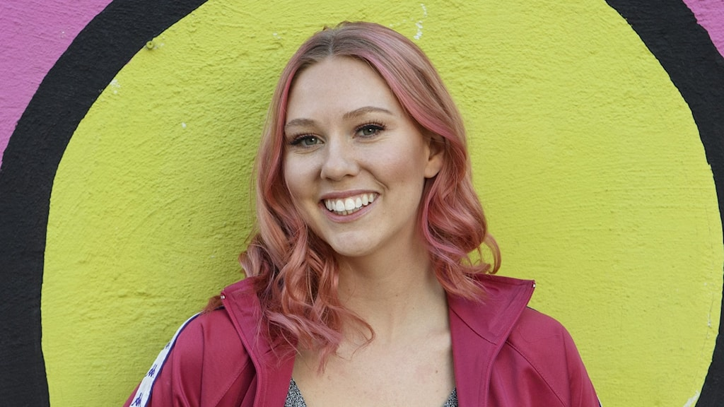 Nya framgångar för Clara Klingenström på Svensktoppen. På bilden: En ung kvinna med rosa hår står framför en vägg i klara färger.