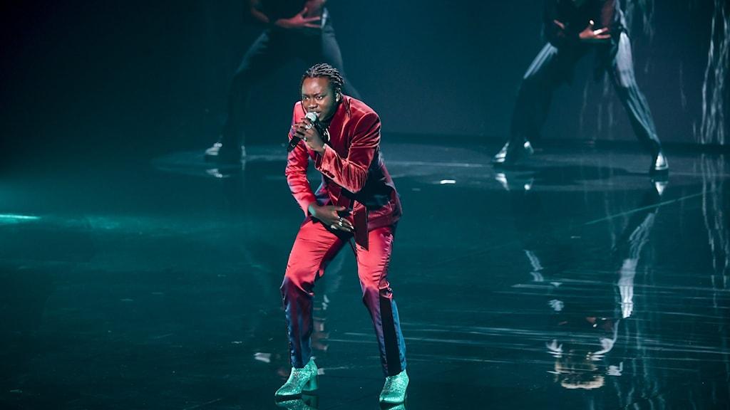 Tusse står på scen med en mikrofon  sin hand.