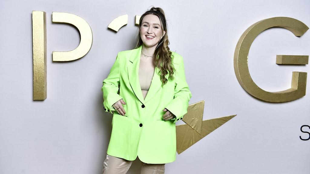 Myra Granberg ser glad ut när hon står och posar med P3 Guld loggan bakom sig.
