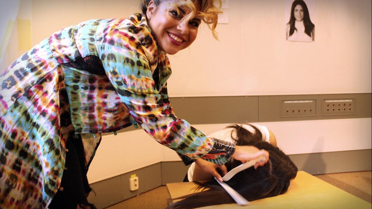 Arantxa visar hur man plattar håret med ett strykjärn. Foto: Gustaf Widegård/SR