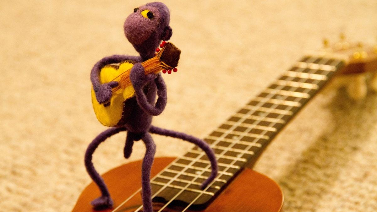 Bild på en plysch-apa som står på en gitarr med en liten låtsasgitarr i famnen. Foto: Helen Cook/Flickr/CC BY-SA 2.0