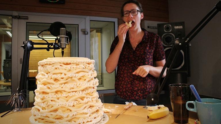 Reporter-Anna stoppar in en stor bit spettekaka i munnen som hon sågat loss från en stor kaka som står på bordet framför henne. Foto: Gustaf Widegård/SR