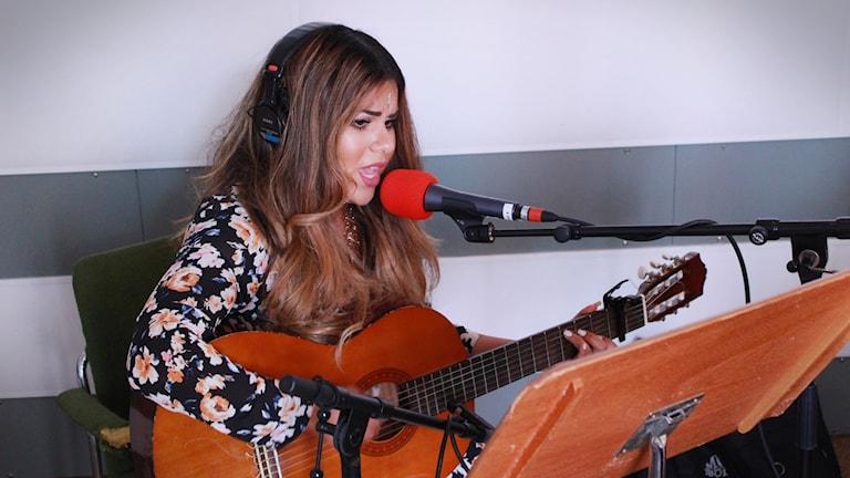 Arantxa sitter med gitarr och sjungar i studion. Foto: Gustaf Widegård/SR