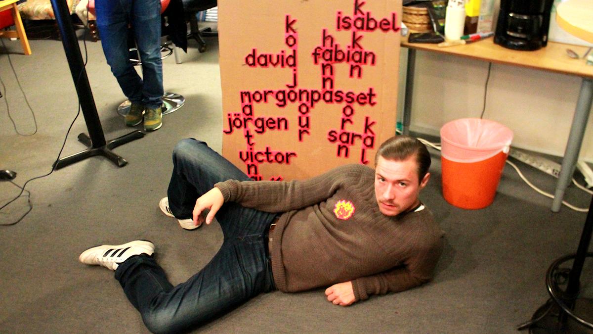 David Druid ligger på golvet framför ett pärlplattekonstverk vi fått av en lyssnare. Foto: Paulo Saka/SR
