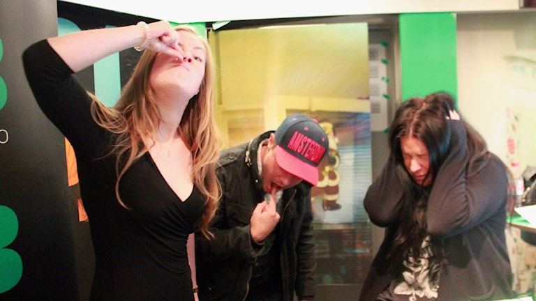 Sara som låtsas ta ut något ur näsan, David som får kväljningar och Martina som ser skärrad ut. Alla tre är i studion.