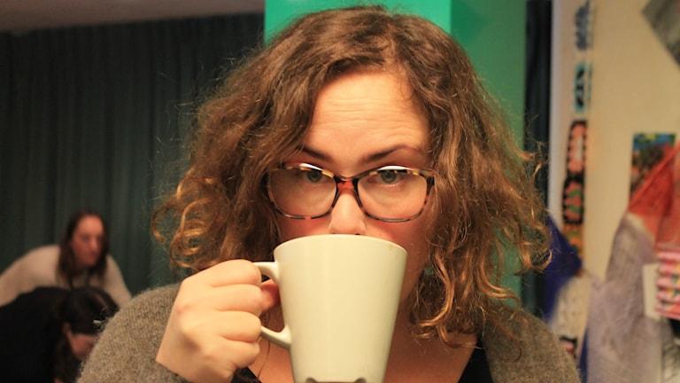 Hanna dricker en kopp kaffe