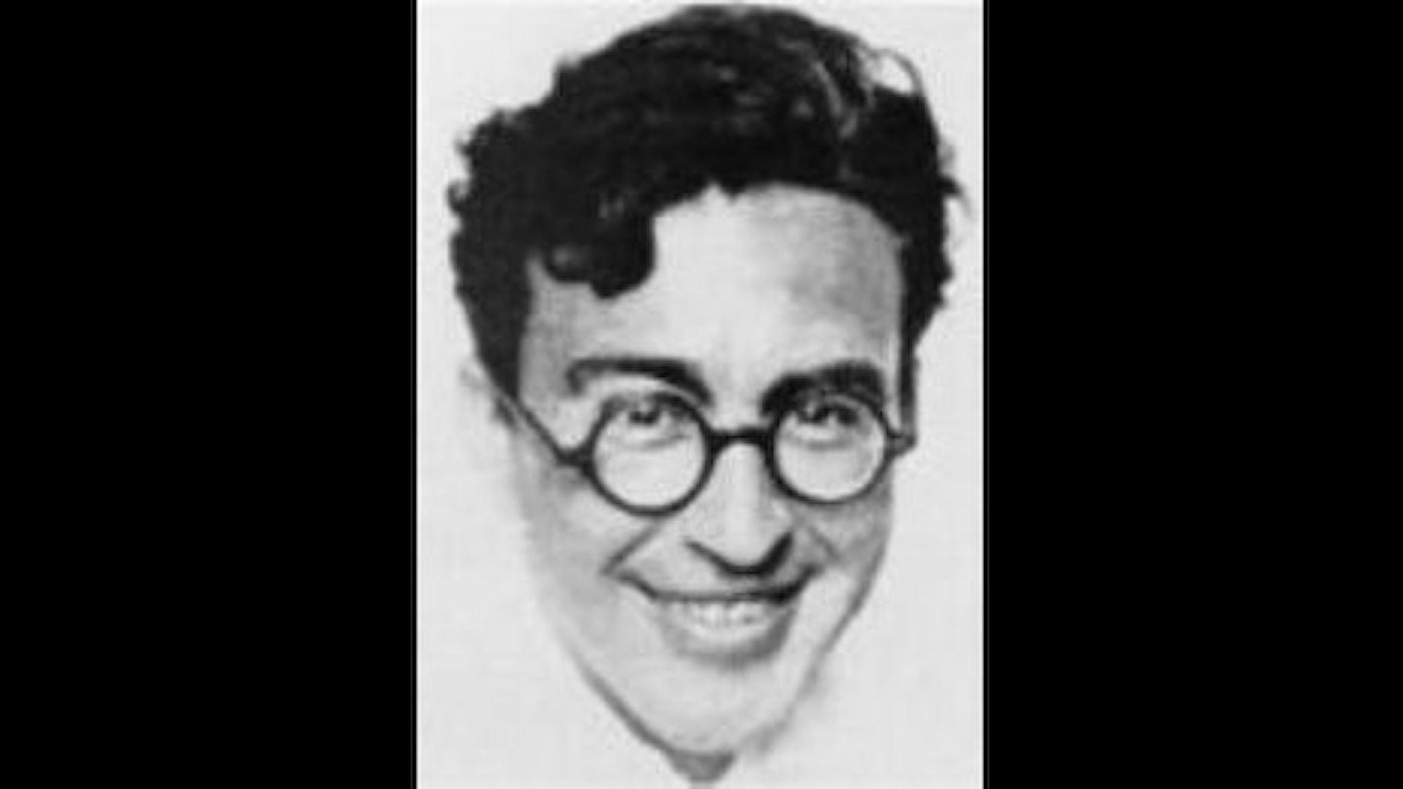 svartvitt profilfoto av en man med mörkt hår och glasögon. Han tittar in i kameran och ler