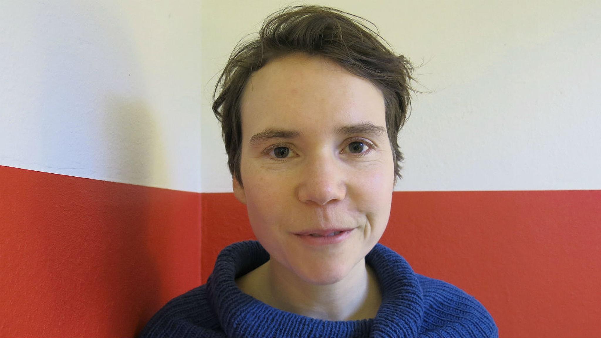 En kvinna i kort hår står med ansiktet framåt, bakgrunden är en vit och röd vägg.