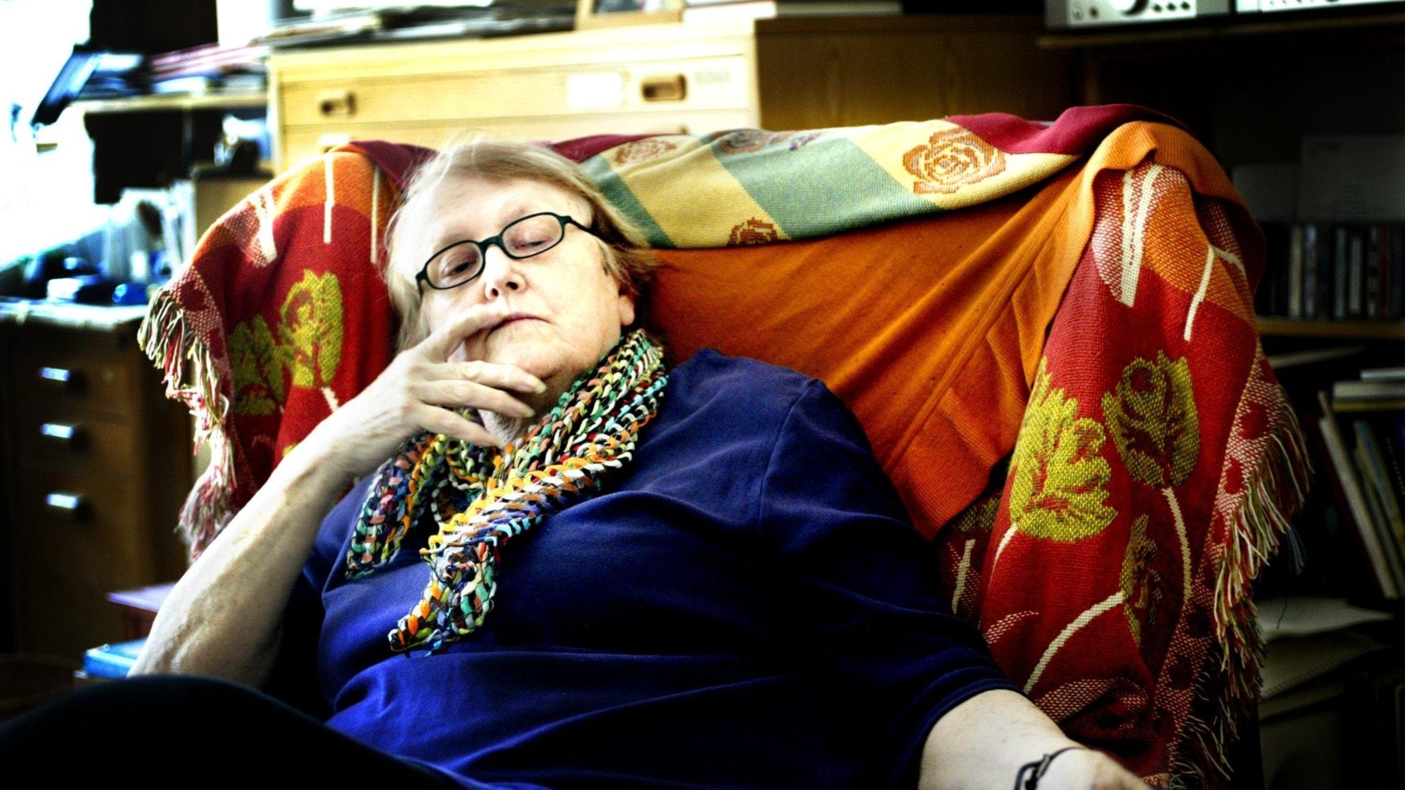 En äldre kvinna sitter i en stol med färgglada sjalar. Hon har ena fingret i mungipan och ser betänksam ut