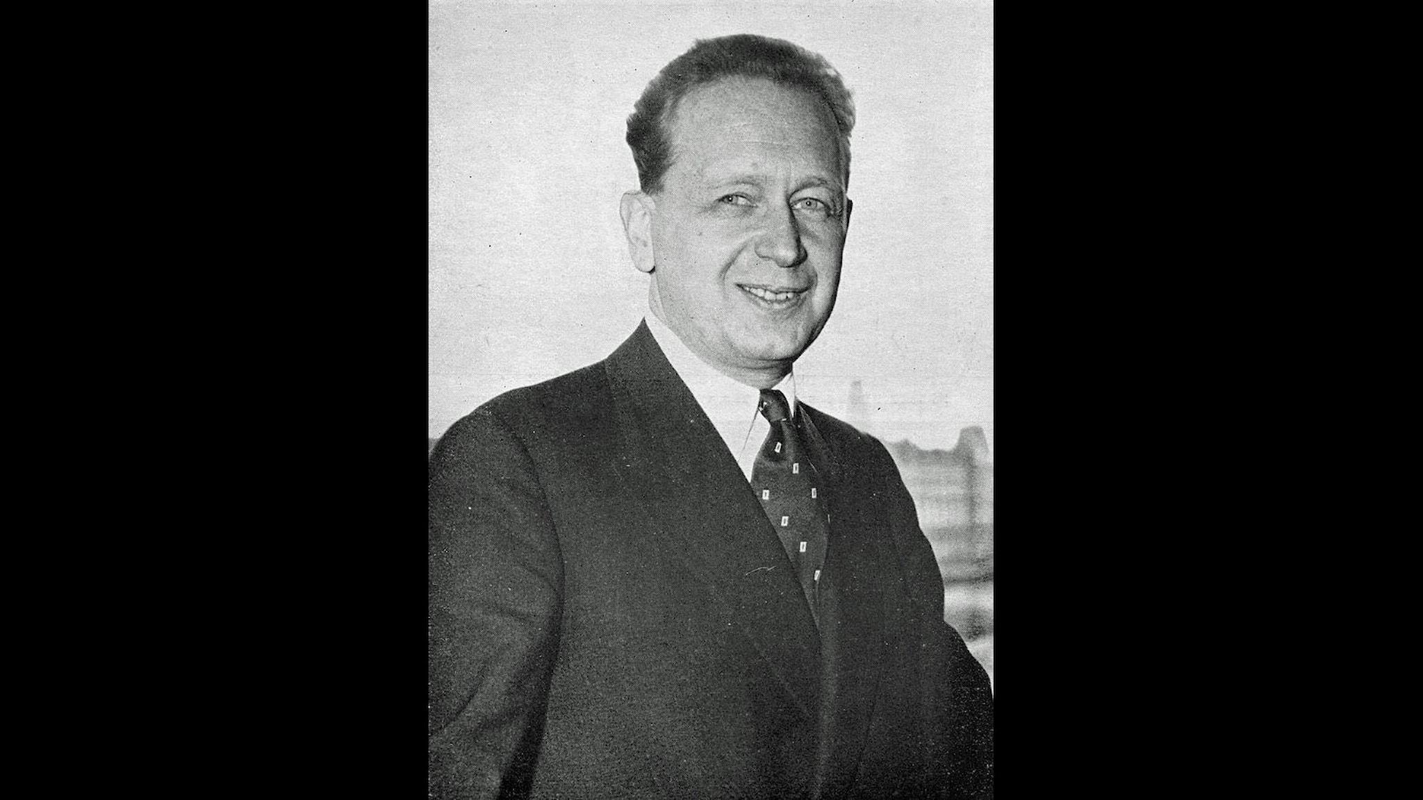 Dag Hammarskjöld står framför kameran i kostym och prickig slips.