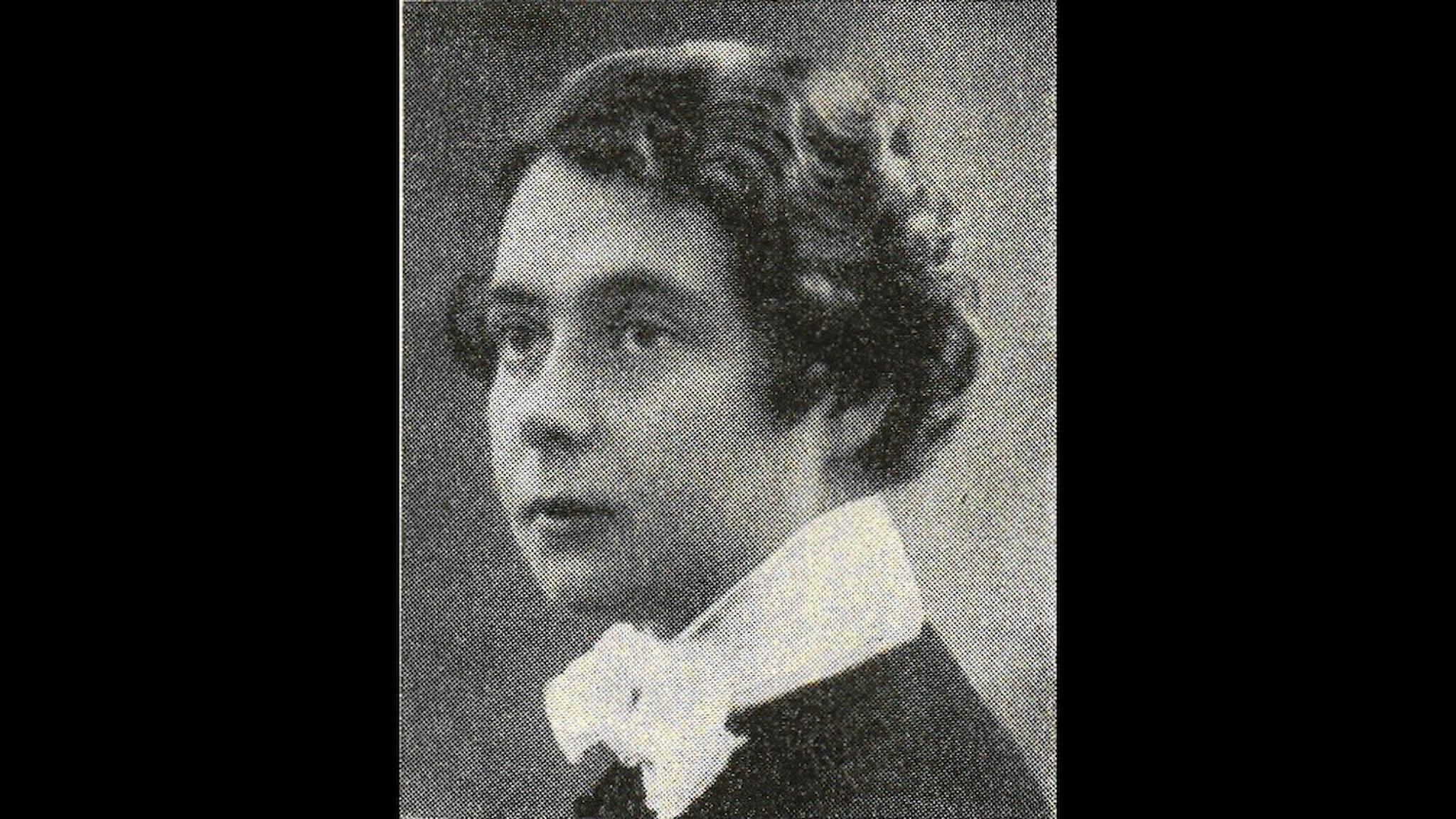 ett gammalt svart vit foto av en kvinna i frisyr. Hon är ung och har håret flätat