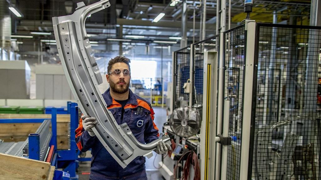 A man handling a big metal part inside a factory.