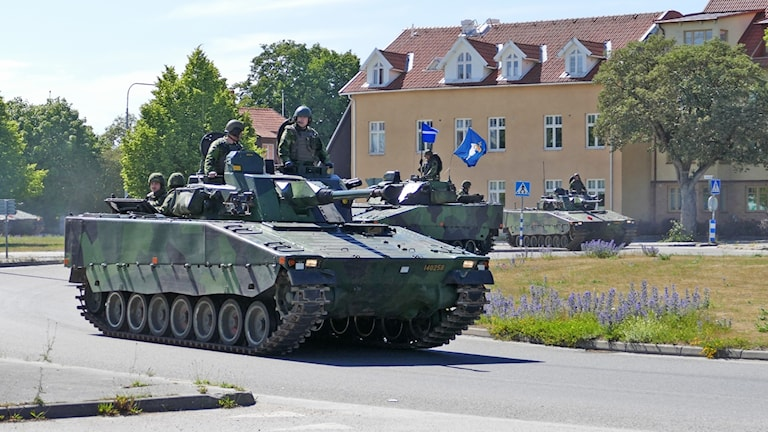 A tank rolling on a road by a house in Gotland.