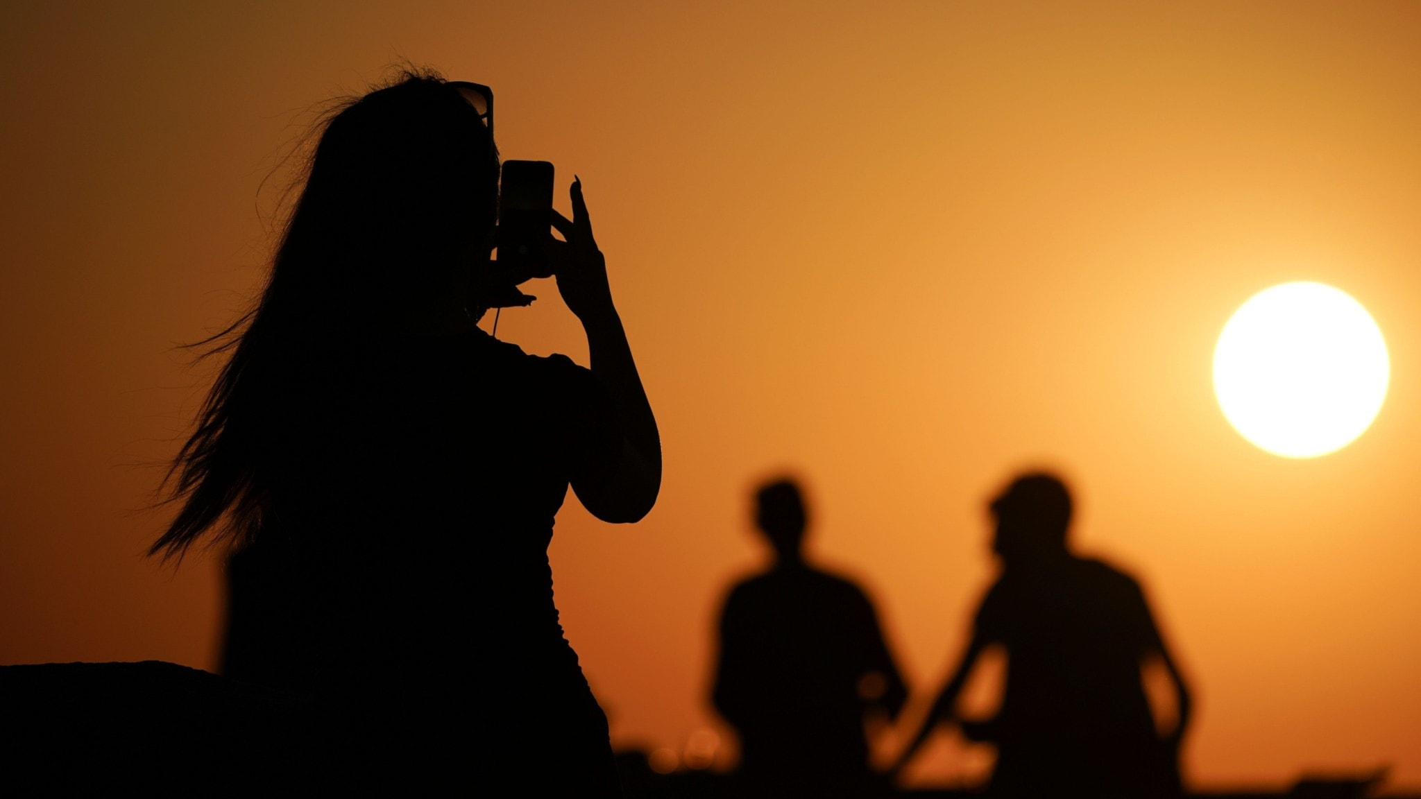 Three people in silhouette against the setting sun. One person holds up her phone, and it looks like she may be taking a picture of the sunset.