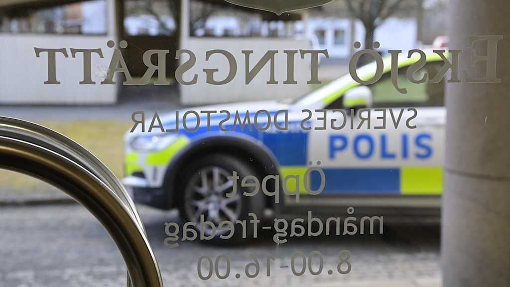 A glass doorway with a logo and lettering on it and a police car seen through it.