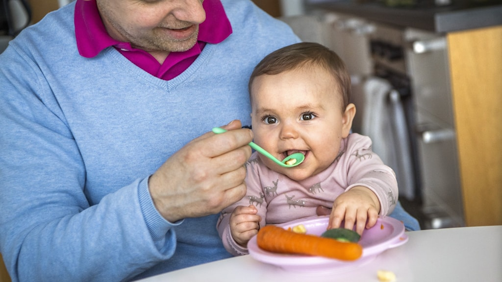A picture of a baby being spoon-fed.