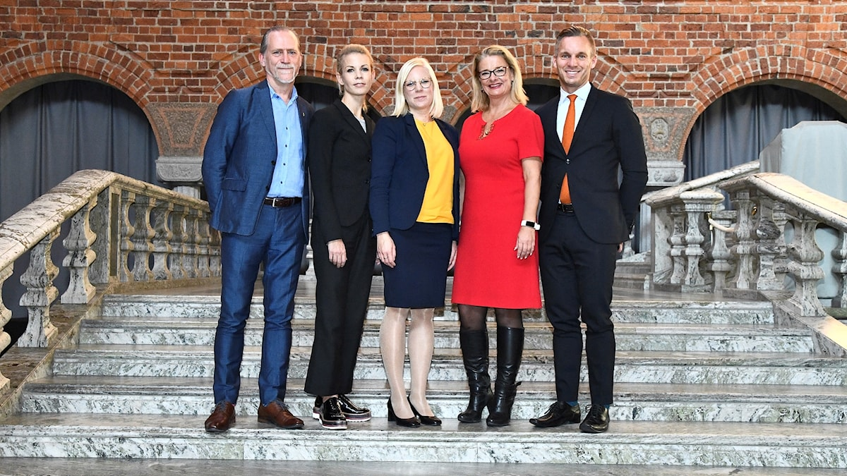 Five politicians on the steps of Stockholm's City Hall.