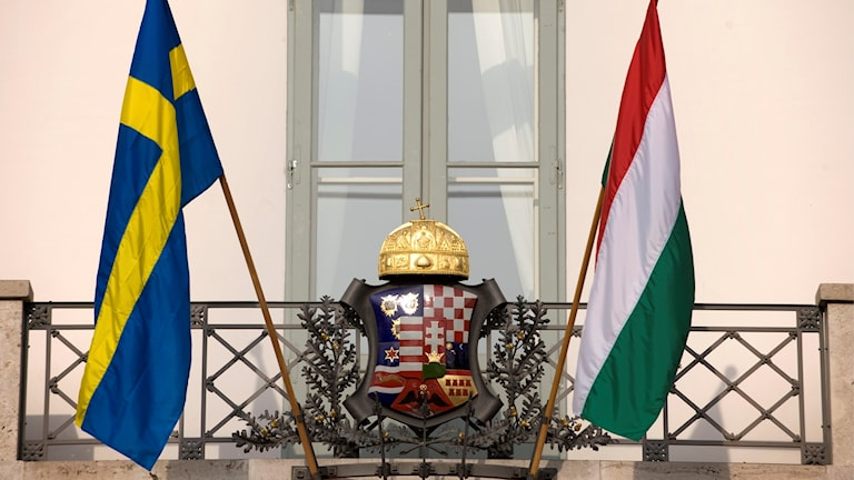 swedish flag and hungarian flag waving from a balcony bearing an insignia topped by a crown