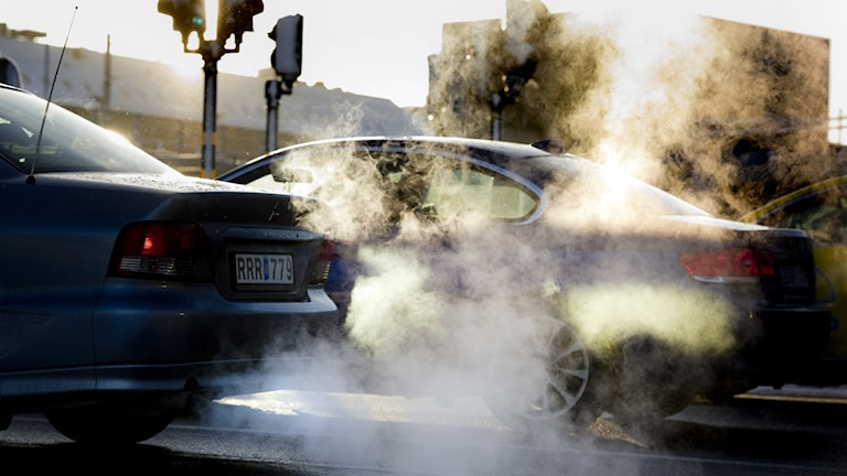 A fog-like smoke coming from and enveloping two cars.