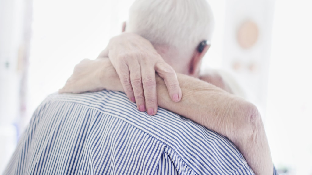 Elderly couple hugging.