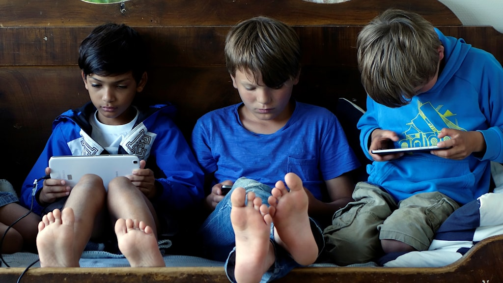 Three young boys with computer tablets.