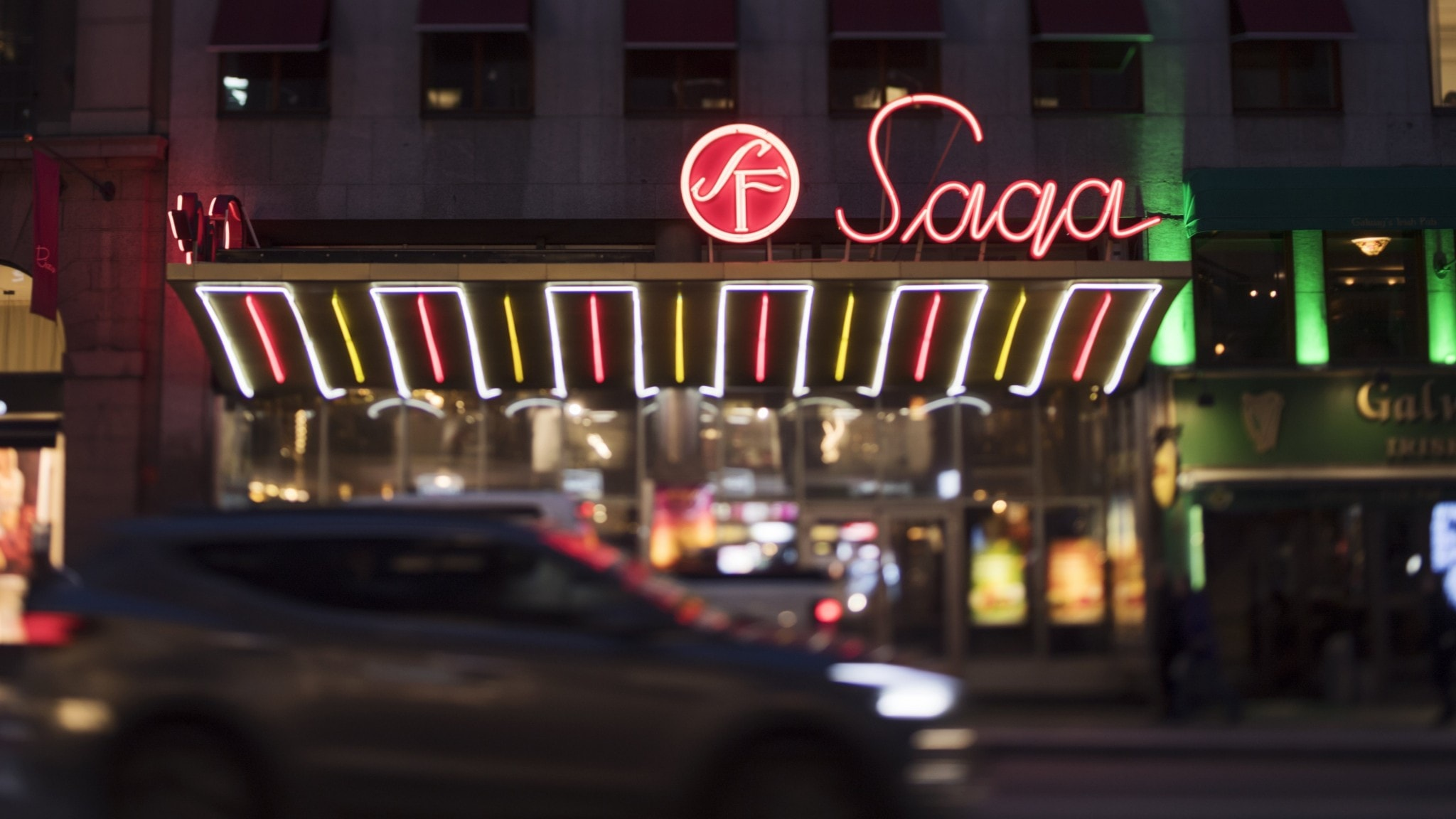 A lit neon sign on a building.