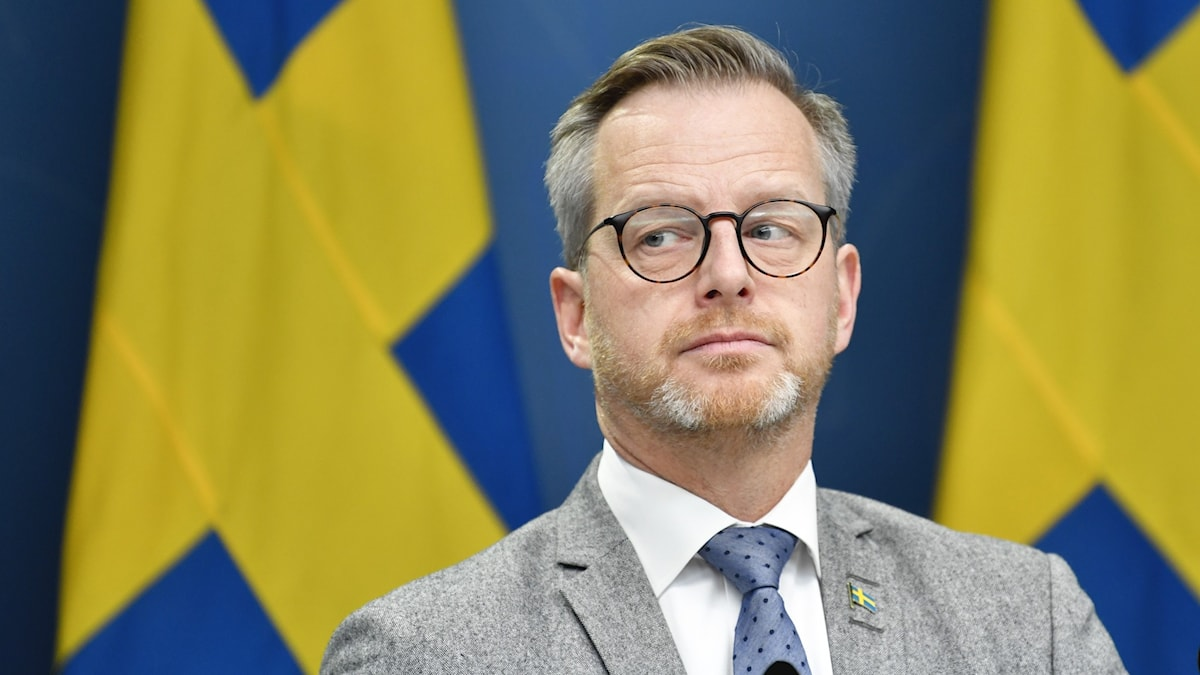 A close-up shot of Home Affairs Minister, Mikael Damberg, who is wearing a gray suit and a blue tie and standing in front of two Swedish flags.