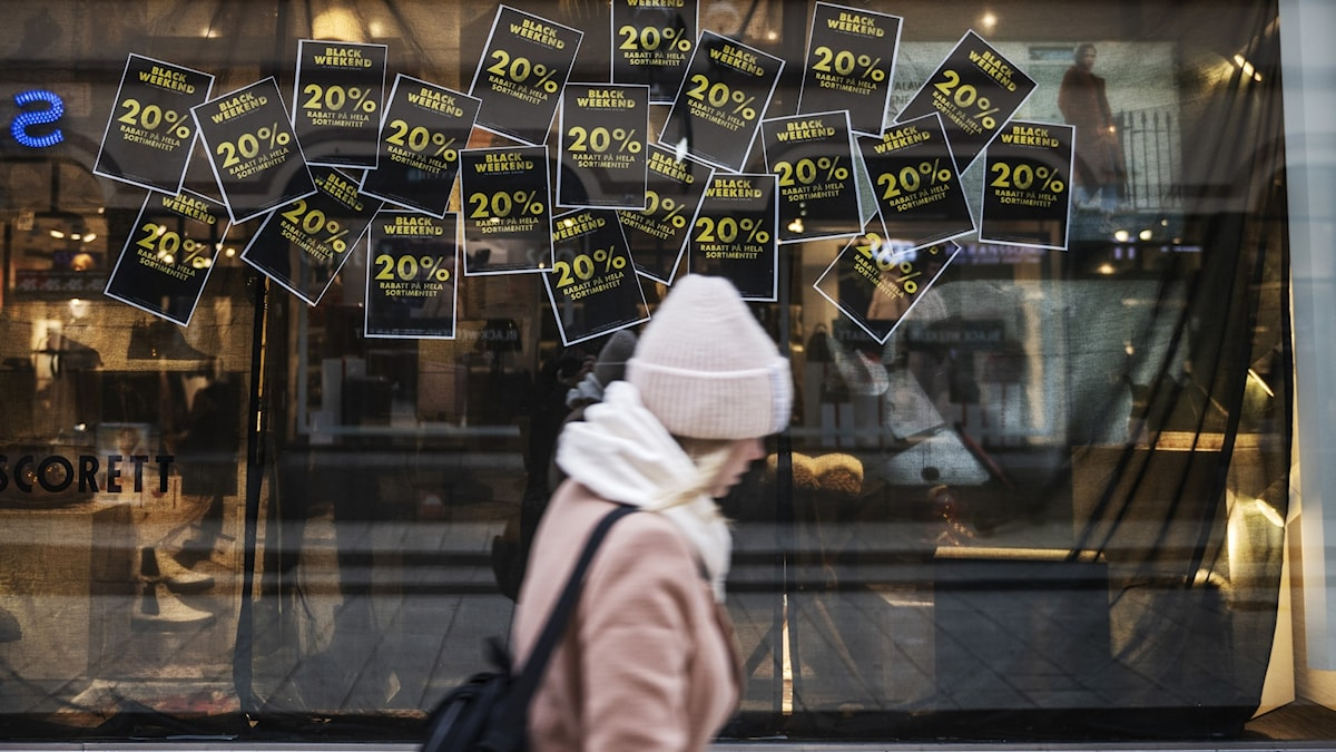 A woman walks past the window of a shop where Black Friday sales are on.