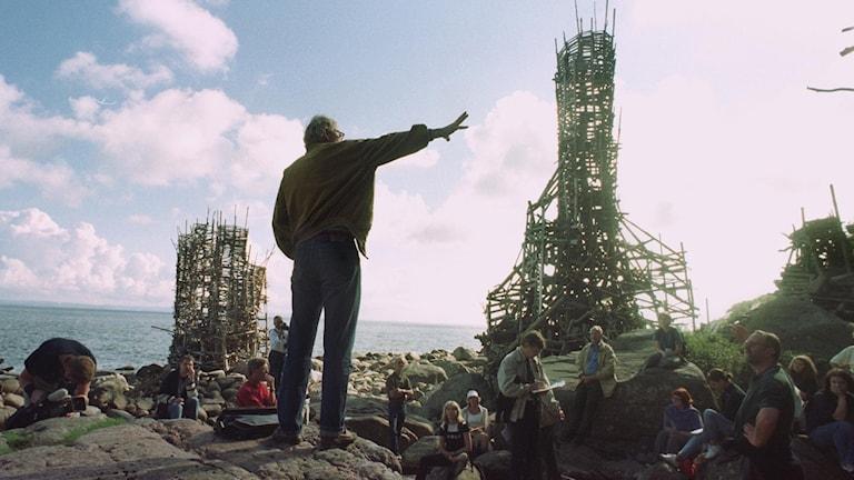 Lars Vilks med ryggen mot kameran pekar på sitt konstverk Nimis, skapat av drivved, i Kullaberg 2001.