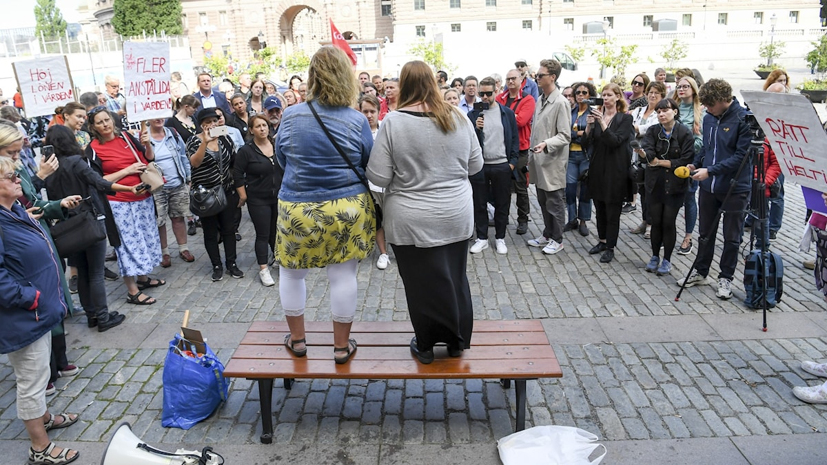 People standing in a semi-circle around two women with their backs to the camera.