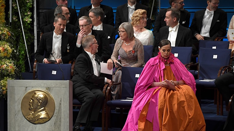 People seated at the Nobel ceremony, with one person wearing a colourful dress.