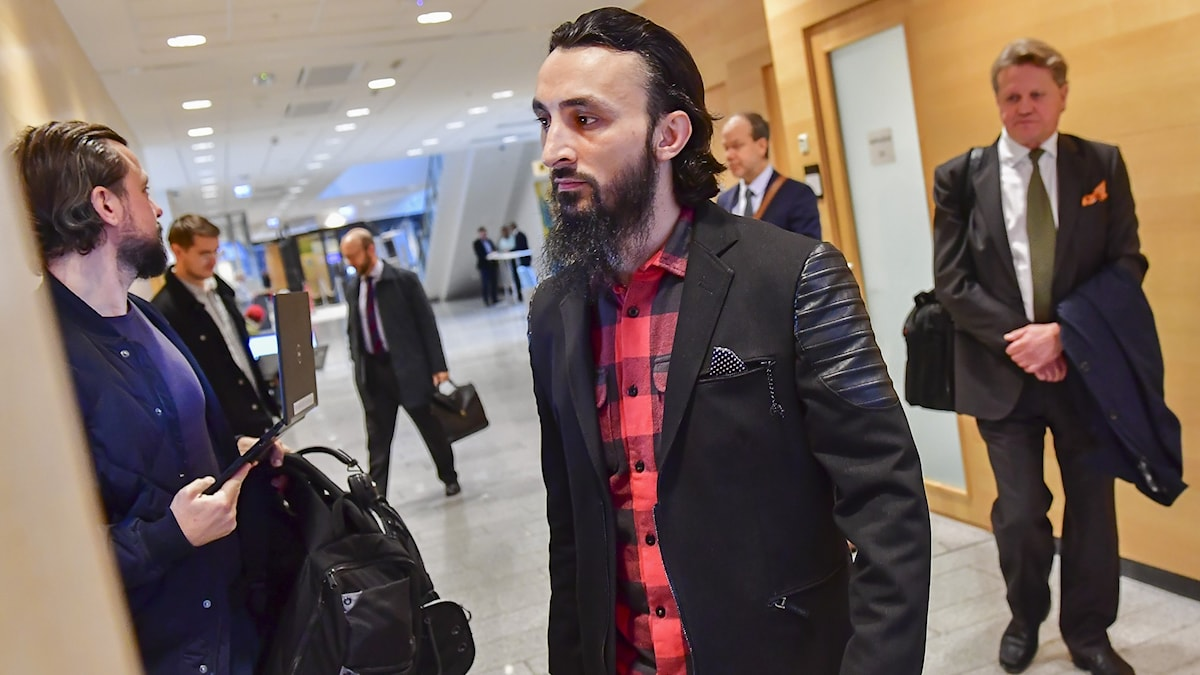 Man with a beard and leather jacket in the corridor of a court.