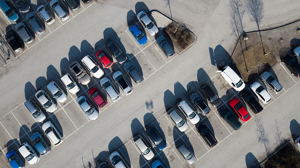 An overhead shot of cars parked in a carpark outdoors.