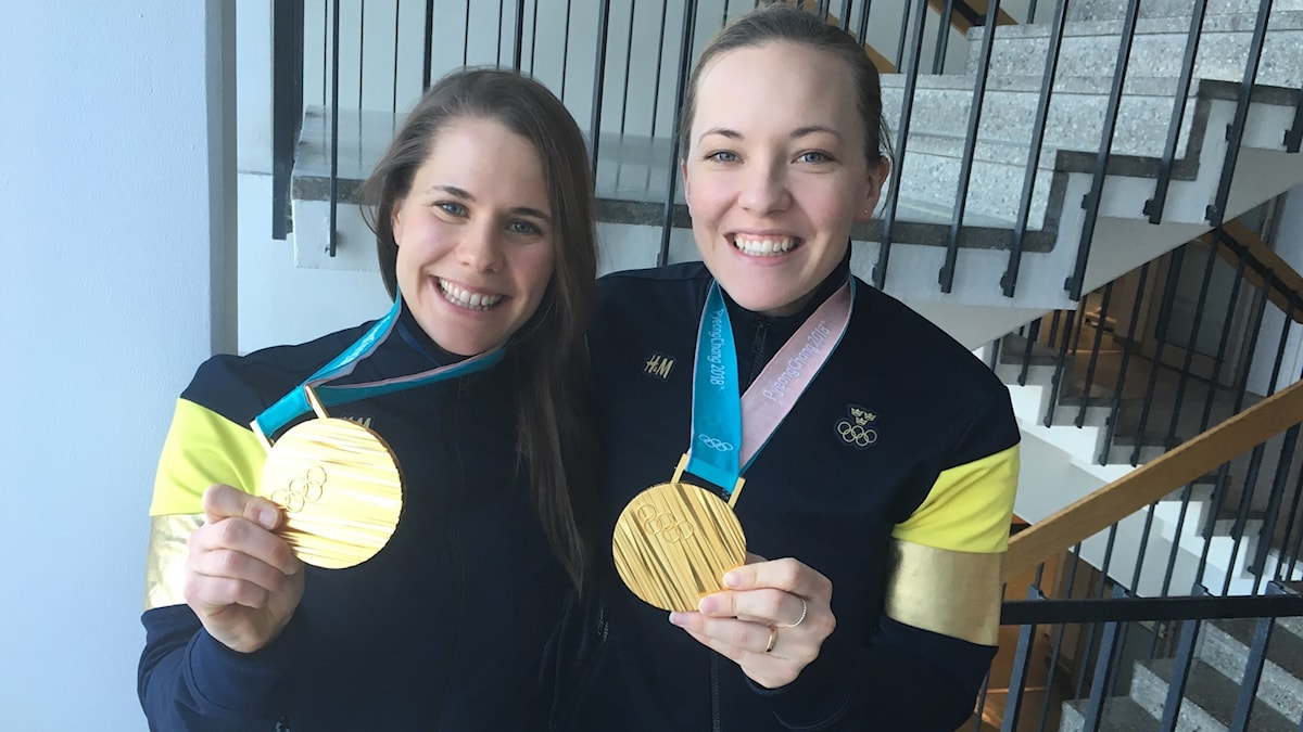 Two people smiling and holding up gold medals, which they are wearing around their necks.