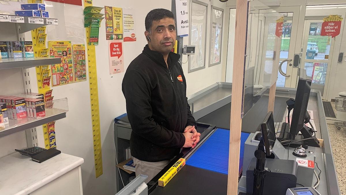 En man från Pakistan står vid kassaapparaten i lanthandeln i Rörvik.