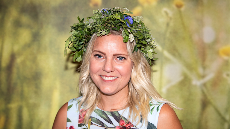 Carina Bergfeldt wearing a midsummer crown for her Sommar show.