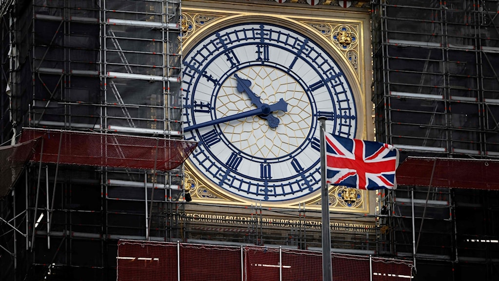 The clock face of Big Ben with a UK flag in the foreground.