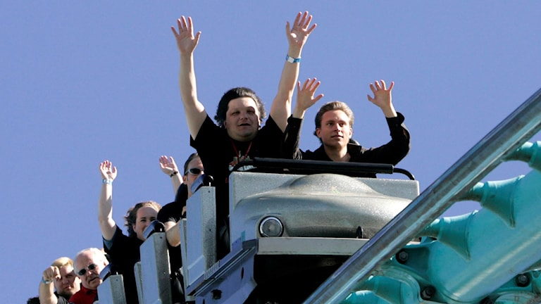 People waving on a rollercoaster