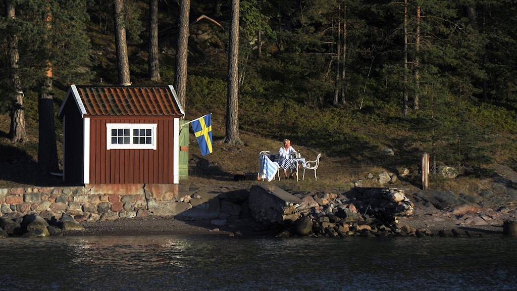Little red cabin with a Swedish flag on the edge of lake. Man sittting at a table outside, in the sunshine.