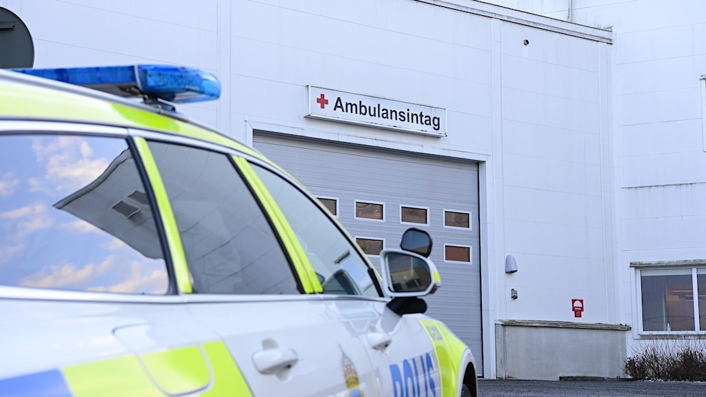 A police car in front of the ambulance-entrance to a hospital.