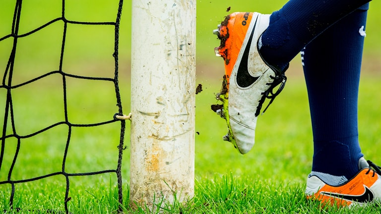 Close up, football shoes against a football goal post.